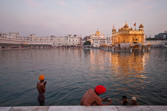 This photograph was shot at The Golden Temple in India. I was lucky enough to arrive early in the morning to capture a lovely light and  two rituals happening simultaneously during morning bathing. One man prays while another  photographs his smiling children.
